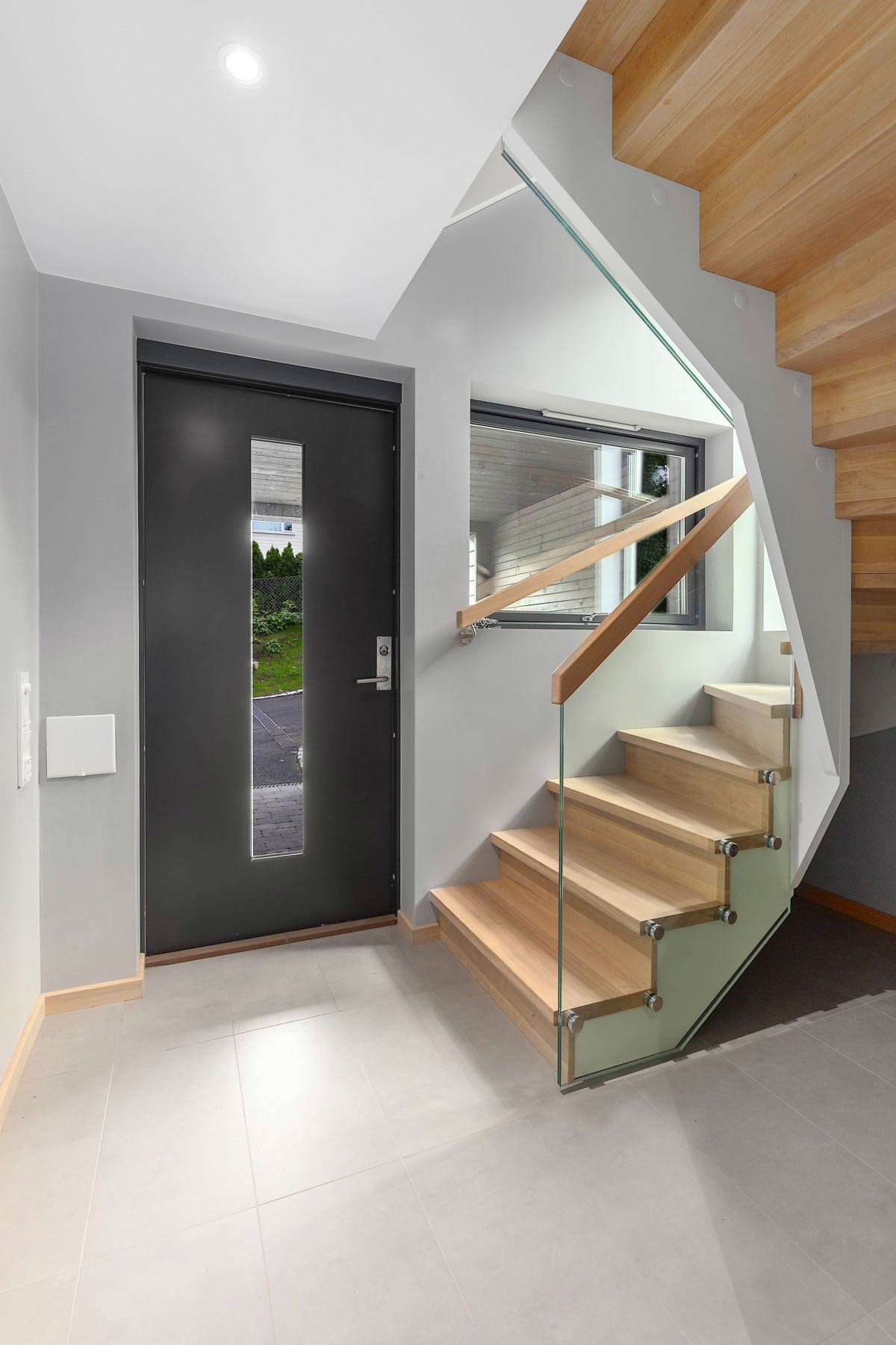 Moderne tretrapp med glassrekkverk og trinn i eik
